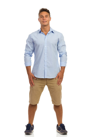 Handsme young man in beige shorts, blue shirt and sneakers standing with legs apart. Front View. Full length studio shot isolated on white.