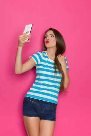puckering lips: Young woman in striped shirt and jeans shorts making a selfie and sending a kiss. Three quarter length studio shot on pink background.