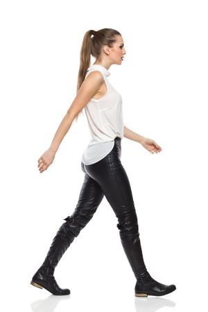 흰 셔츠와 검은 가죽 바지에 산책하는 젊은 여자. 측면보기. 전체 길이 스튜디오에 격리 된 흰색을 쐈 어.