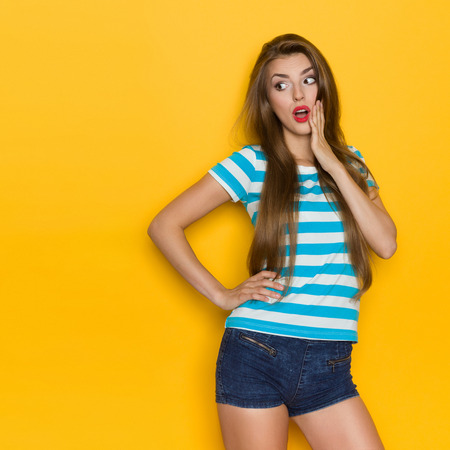 Surprised young woman with long brown hair, blue striped shirt and jeans shorts looking at copy space and holding hand on chin. Three quarter length studio shot on yellow background.