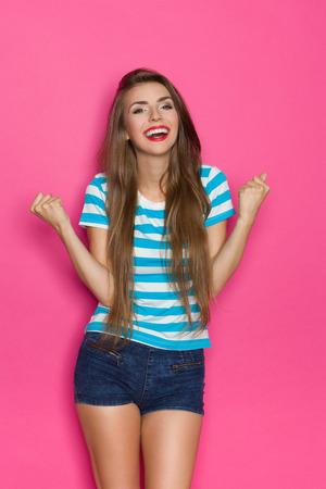 Sourire belle jeune femme aux cheveux longs posant avec les poings levés. Trois studio trimestre longueur tourné sur fond rose.