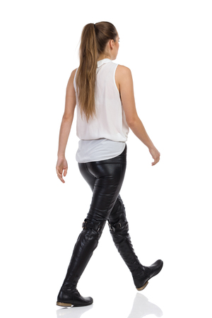 Young woman walking in white shirt, black leather trousers and black boots. Rear side view. Full length studio shot isolated on white.