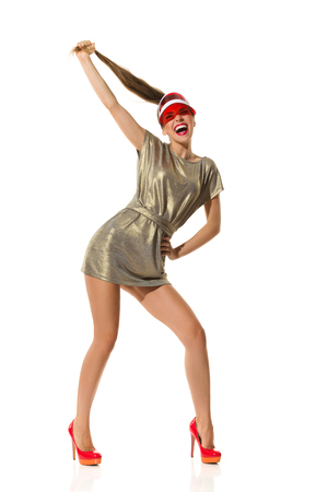 visor: Laughing young woman in gold mini dress, red high heels and sun visor cap pulls her long hair. Full length studio shot isolated on white.