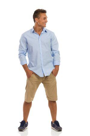 주머니에 손을 잡고 멀리 찾고, 베이지 색 반바지, 파란색 셔츠와 떨어져 다리 서 운동화 젊은 남자 웃고. 전체 길이 스튜디오 샷 화이트에 격리입니다.
