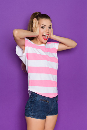 Young woman in pink striped shirt and jeans shorts holds head in hands and shouting. Three quarter length studio shot on violet background.