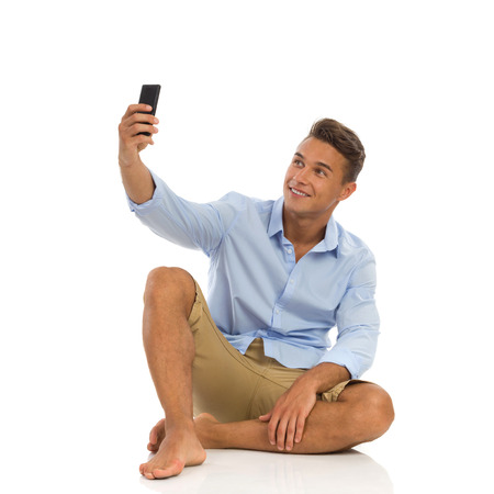 unbuttoned: Young man in unbuttoned white shirt and jeans shorts sitting on a floor holding smartphone and taking a selfie. Full length studio shot isolated on white.