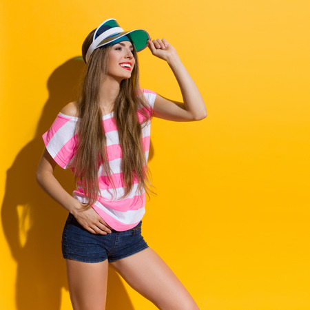 three quarter length: Smiling young woman in pink striped shirt and jeans shorts holding blue sun visor and looking away. Three quarter length studio shot on yellow background.