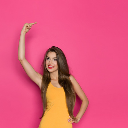 waist shot: Beautiful young woman in orange shirt pointing over her head. Waist up studio shot on pink background.