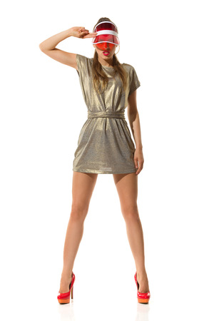 legs apart: Serious young woman in gold mini dress, red high heels and sun visor cap standing with legs apart and salute. Full length studio shot isolated on white.