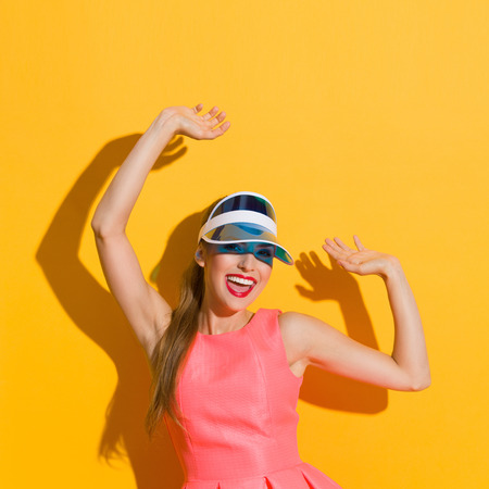 three quarter length: Shouting young woman in pink dress and sun visor posing with arms raised. Three quarter length studio shot against yellow background.
