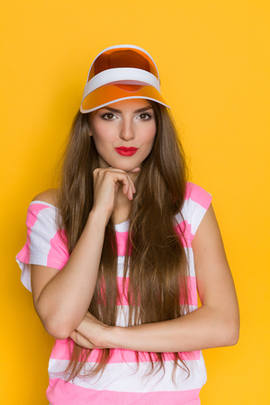 visor: Cheerful young woman in pink striped shirt and orange sun visor posing with hand on chin. Waist up studio shot on yellow background.