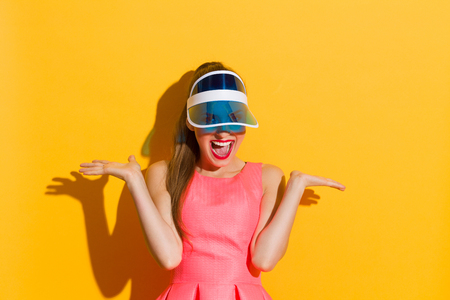 visor: Shouting young woman in pink dress and sun visor posing with arms outstretched. Waist up studio shot against yellow background. Stock Photo