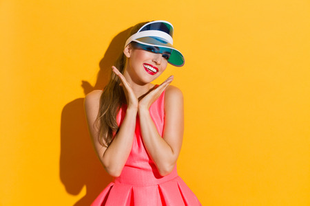 waist shot: Beautiful young woman in pink dress and sun visor posing with hands close to a chin. Waist up studio shot on yellow background. Stock Photo