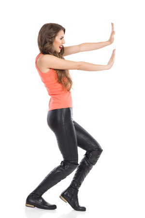 strong women: Young smiling woman pushing imaginary wall. Side view. Full length studio shot isolated on white.