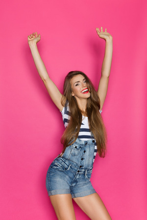 dungarees: Laughing young woman in dungarees posing with arms raised. Three quarter length studio shot on pink background.