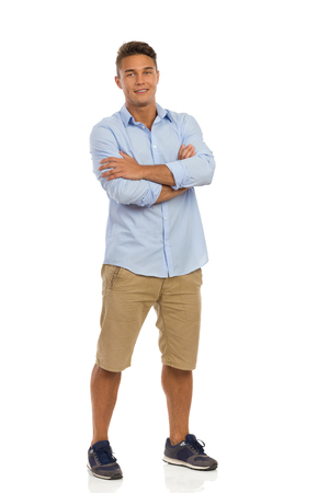 Handsome young man in beige shorts, blue shirt and sneakers standing with arms crossed. Full length studio shot isolated on white.