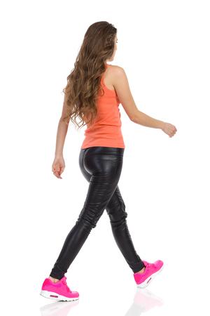 Jonge vrouw lopen in oranje shirt en een zwart lederen broek. Side zicht naar achteren. Full length studio shot geïsoleerd op wit.