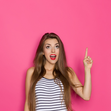 waist shot: Surprised beautiful young woman in striped shirt looking up and pointing. Waist up studio shot on pink background. Stock Photo