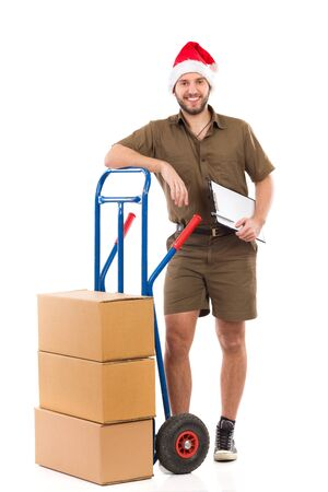 leaning on the truck: Smiling delivery man in santa hat standing close to a push cart and holding a clipboard. Full length studio shot isolated on white. Stock Photo