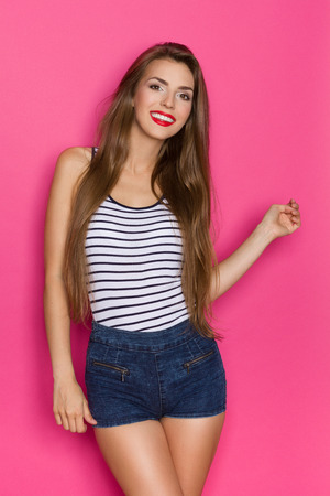 three quarter length: Smiling beautiful young woman with long hair posing. Three quarter length studio shot on pink background.