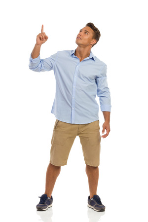 standing up: Young man in beige shorts, blue shirt and sneakers standing, pointing up and looking. Full length studio shot isolated on white. Stock Photo