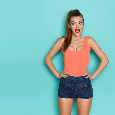 Surprised young woman in orange shirt and jeans shorts standing with hands on hip and looking away. Three quarter length studio shot on teal background.