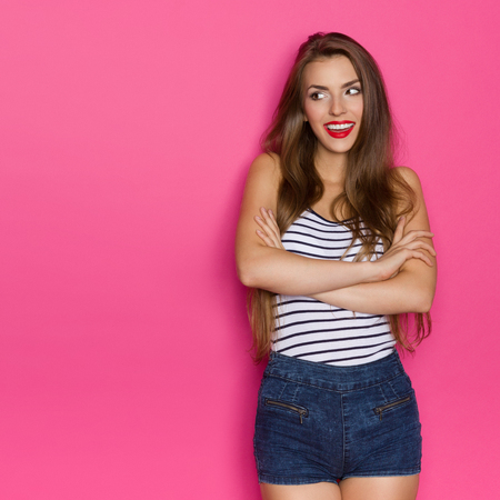 three quarter length: Smiling beautiful young woman with long hair posing with arms crossed and looking at copy space. Three quarter length studio shot on pink background. Stock Photo