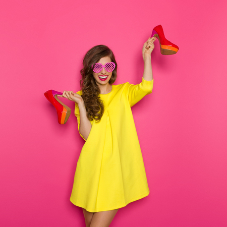 three quarter length: Happy young woman in yellow mini dress and pink sunglasses holding a red high heels shoes. Three quarter length studio on pink background. Stock Photo