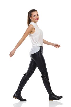 白いシャツに黒の革のズボンで歩いている若い女性。側面図です。完全な長さのスタジオ撮影に分離白。