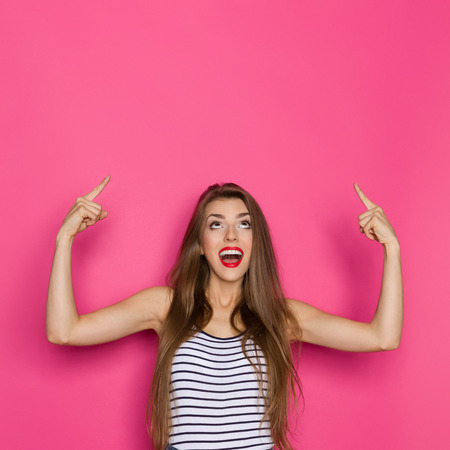 waist shot: Shouting beautiful young woman in striped shirt looking up and pointing. Waist up studio shot on pink background.