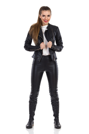 legs apart: Smiling young woman in black leather trousers, jacket and boots standing with legs apart and looking at camera. Full length studio shot isolated on white.