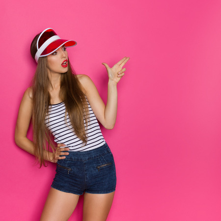 Young woman in striped shirt and red sun visor showing finger gun. Three quarter length studio shot on pink background.