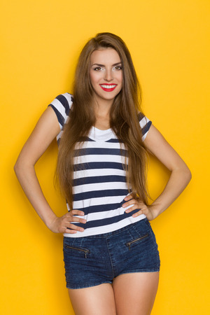 three quarter length: Beautiful young woman with long brown hair posing in blue striped shirt and jeans shorts and holding hands on hip. Three quarter length studio shot on yellow background.