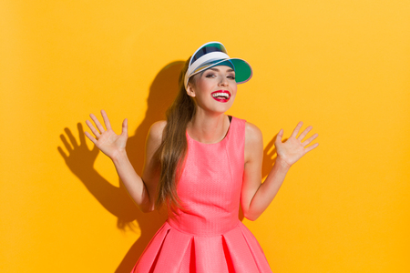 visor: Laughing young woman in pink dress and sun visor posing with arms outstretched. Waist up studio shot against yellow background. Stock Photo