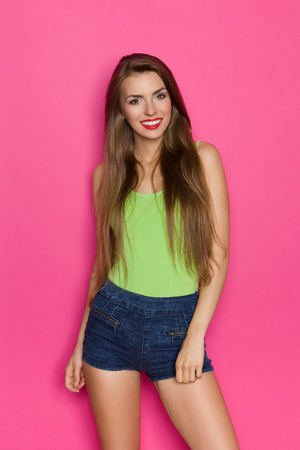 three quarter length: Smiling girl in lime green shirt and jeans shorts posing. Three quarter length studio shot on pink background. Stock Photo