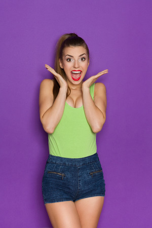 three quarter length: Beautiful young woman in lime green shirt and jeans shorts standing with hands raised and shouting. Three quarter length studio shot on violet background.