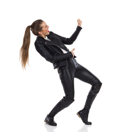 Shouting young woman in black leather trousers, jacket and boots playing the air guitar and looking away. Side view. Full length studio shot isolated on white.