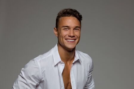 unbuttoned: Smiling young man in white unbuttoned shirt. Studio portrait on gray background.