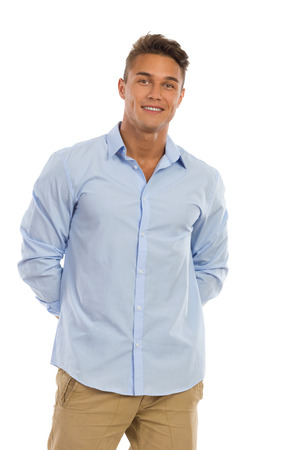 staring at the camera man: Smiling young man in blue shirt staning and holding hands behind back. Three quarter length studio shot isolated on white.