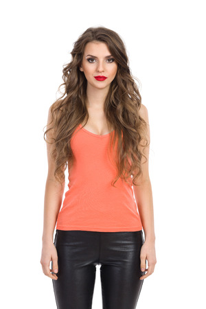 three quarter: Young woman in leather trousers, orange shirt posing. Three quarter length studio shot isolated on white. Stock Photo