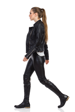 ponytail: Sexy young woman in black leather trousers, boots and jacket walking and looking away. Full length studio shot isolated on white. Stock Photo
