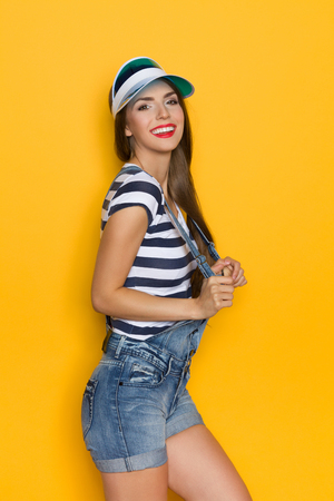 visor: Beautiful young woman in dungarees, blue striped shirt and plastic sun visor posing. Three quarter length studio shot on yellow background. Stock Photo
