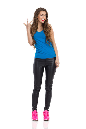 Cheerful young woman in blue shirt, black leather trousers, and pink sneakers standing and showing three fingers. Full length studio shot isolated on white. Stock Photo