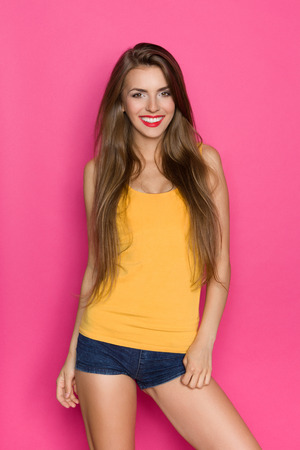 pink posing: Young woman in orange shirt and jeans shorts posing against pink background.