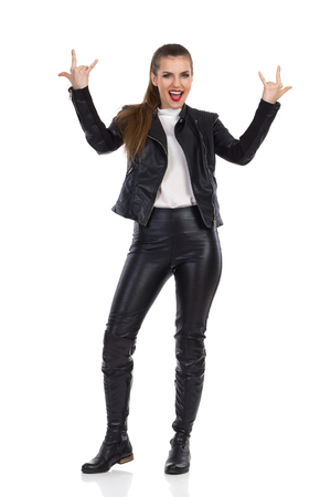 Shouting young woman in black leather trousers, jacket and boots standing with arms outstretched and showing rock hand sign. Full length studio shot isolated on white. Stock Photo