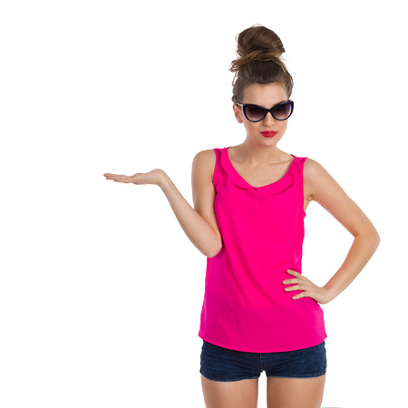 Smiling young woman with hair bun in sunglasses pink shirt, jeans shorts and pink sneakers standingwith hand raised and presenting. Three quarter length length studio shot isolated on white. 免版税图像