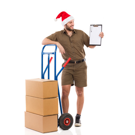 leaning on the truck: Happy delivery man in santa hat standing close to a push cart and holding a clipboard. Full length studio shot isolated on white. Stock Photo