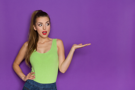 waist shot: Beautiful young woman in lime green shirt and jeans shorts holding open hand. Waist up studio shot on violet background. Stock Photo