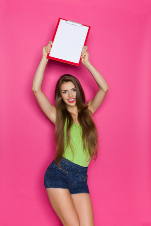 arms above head: Smiling young woman holding clipboard above her head. Three quarter length studio shot on pink background. Stock Photo