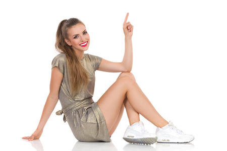 persona sentada: mujer joven en mini vestido de oro y zapatillas de deporte blancas que se sientan en el suelo, mirando a la c�mara y apuntando hacia arriba sonriendo. Estudio de longitud completa aislado disparo en blanco. Foto de archivo